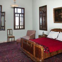 3. Το δωμάτιο φιλοξενίας με την ιδιαίτερα φροντισμένη επίπλωση. / The guest bedroom is adorned with antique furniture, paintings, an elegant sofa and large carpets.